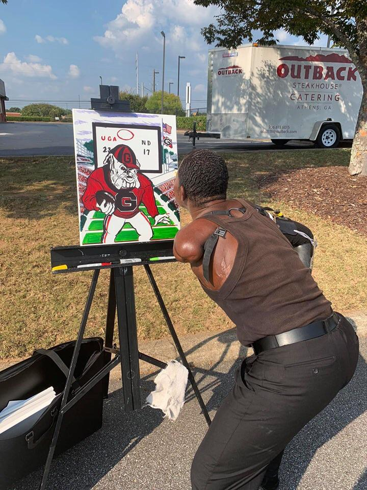 A guy in my hometown who has no arms, draws pictures with his mouth on every college game day.